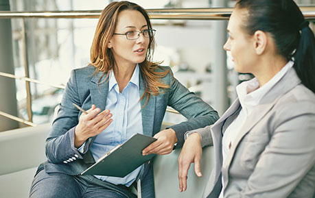 two corporate women discussing seriously