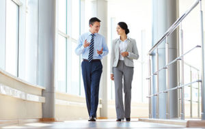 corporate man and woman walking in the office