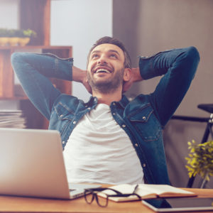 guy happy and relaxing in front of laptop