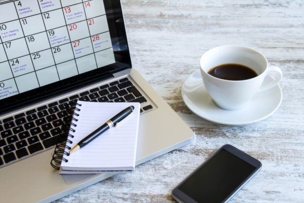 online calendar, notepad, pen, coffee and mobile phone