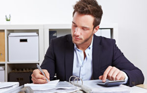 corporate man using calculator and taking notes