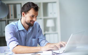corporate man typing in front of computer